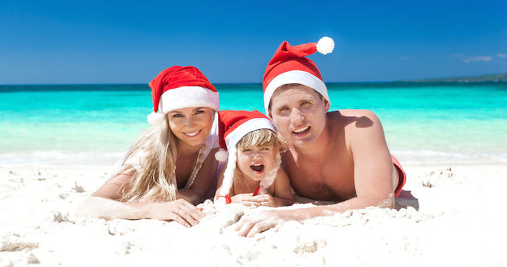 Man, woman and child laying on the beach wearing santa hats
