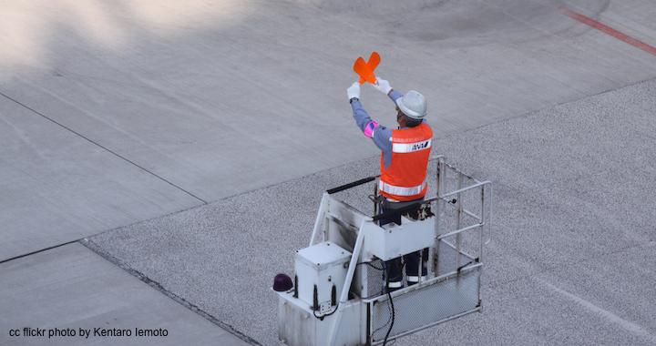 Airplane marshaller directing an airplane