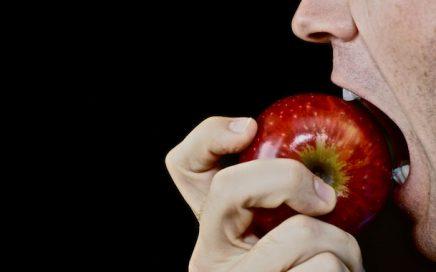 man biting into an apple
