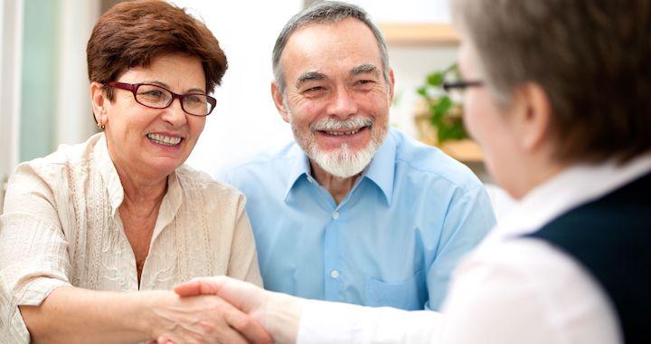 senior couple smiling while shaking hand with service advisor